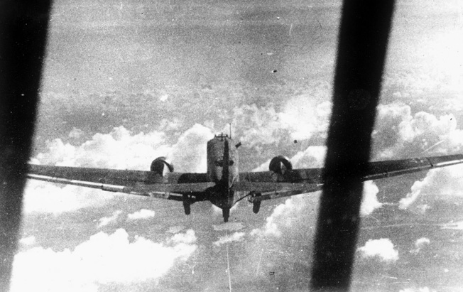 Photographed in flight from another aircraft, a Ju-52 transport plane laden with supplies wings its way to a destination near the front lines in North Africa.