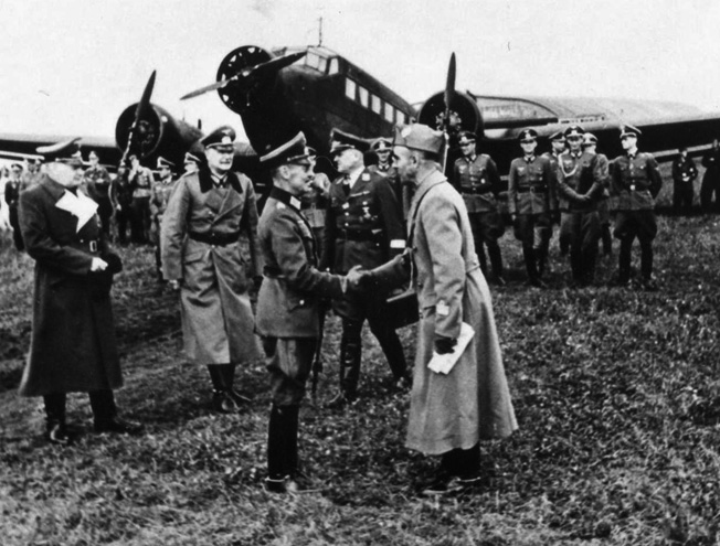 With a Ju-52 transport in the background, Field Marshal Gerd von Runstedt meets an Italian officer at an airfield. The Ju-52 carried personnel on long trips while also serving as the primary air transport for the resupply of the German Army.