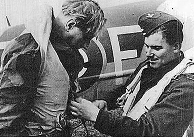 "Flight Lieutenant J.A. Bradley adjusts the Mae West flotation device of Wing Commander Percy ""Pick"" Pickard prior to takeoff for the attack on Amiens Prison. Both veterans of numerous Royal Air Force operations, the fliers were killed in action during the raid."