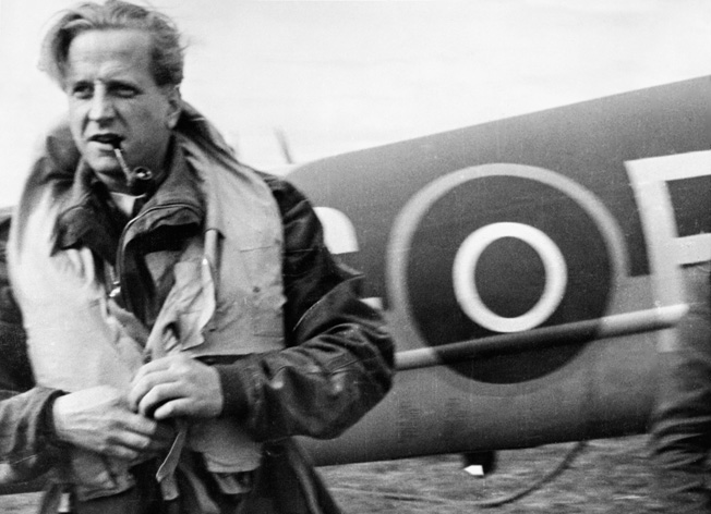 Pickard clenches his pipe between his teeth while standing in front of his de Havilland Mosquito bomber.