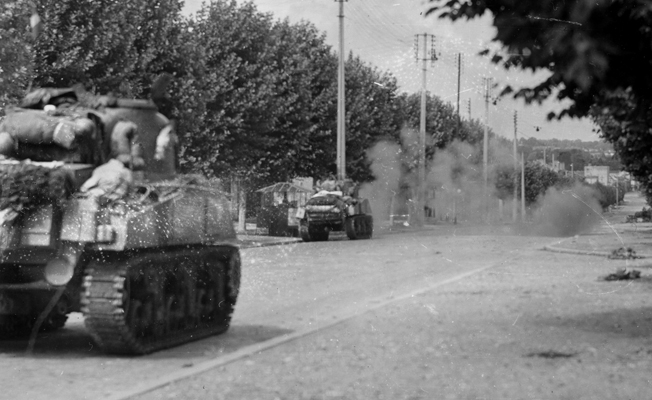 On the outskirts of Paris on August 25, 1944, French tanks roll down a tree-lined boulevard en route to the city as German artillery shells explode dangerously nearby.