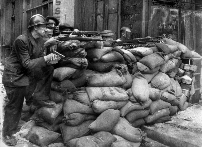A barricade of sandbags provides some cover for French Partisans armed with rifles and automatic weapons as they rise up against the Nazi occupiers of Paris.