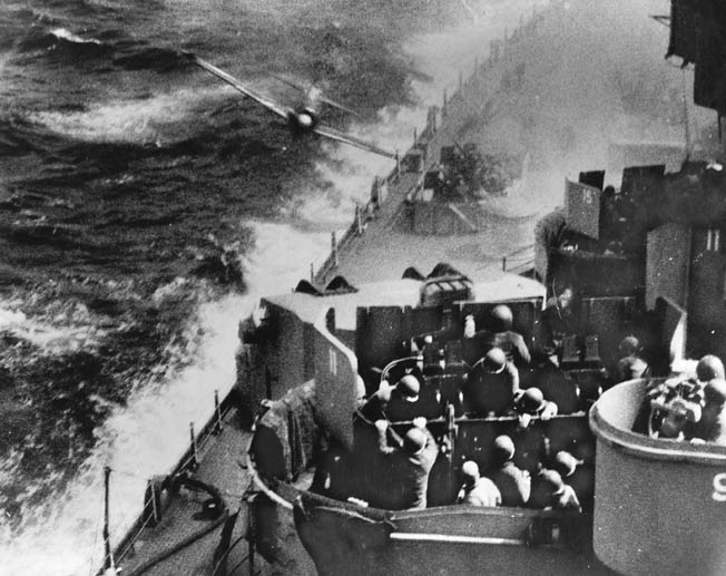 This famous photo depicts the moment of impact as a Japanese Kamikaze hits the hull of the battleship USS Missouri as sailors continue to service their antiaircraft weapons. The A6M2 Zero fighter glanced off the battleship and crashed into the sea moments after the photo was taken.