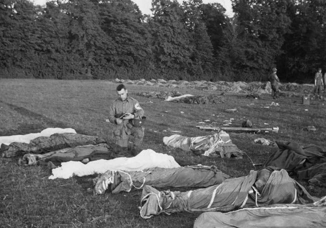 Kneeling in a temporary burial site on the grounds of the Château de Colombière, Father Sam grants absolution to paratroopers of the 101st Airborne Division who have been killed in action or have died of wounds. The cemetery had been established by a group of glider pilots as they awaited transportation back to England, and eventually 188 Germans and 249 Americans were temporarily interred there. Among the Americans were Tech 5 Norman Dick, Corporal Elbert Yeager, and Sergeant Lowell Norwood. The bodies of the Americans were later transferred to a cemetery in Blosville, while the Germans were reinterred in Orglandes.
