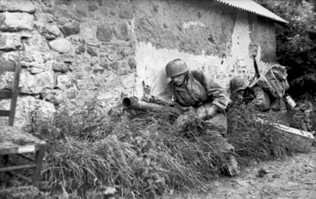 Crouching beside the wall of a farm building in Normandy, two members of Fallschirmjäger Regiment 6 attempt to avoid detection by Allied fighter bombers. The paratrooper at left is carrying a Raketenpanzerbüchse 54, popularly known as the Panzerschreck (an antitank weapon comparable to the American bazooka), while the man at right appears to be carrying a case of ammunition for the weapon.
