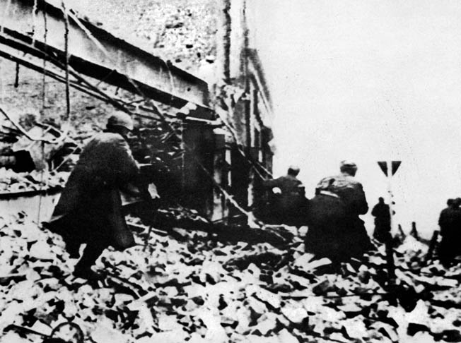 During their rapid advance against the retreating Germans in the winter of 1945, Soviet troops of the 1st Ukrainian Front rush through the rubble of the town of Gleiwitz, Poland.