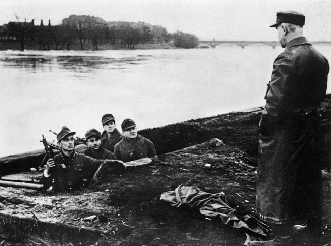 Soldiers of the German Volkssturm listen to orders from an officer as they prepare to man positions along the banks of the Oder River. This photo was taken in early February 1945, and by that time the Volkssturm, essentially old men and boys, had been pressed into service in a futile attempt to stop the Red Army advance into the heart of Nazi Germany.