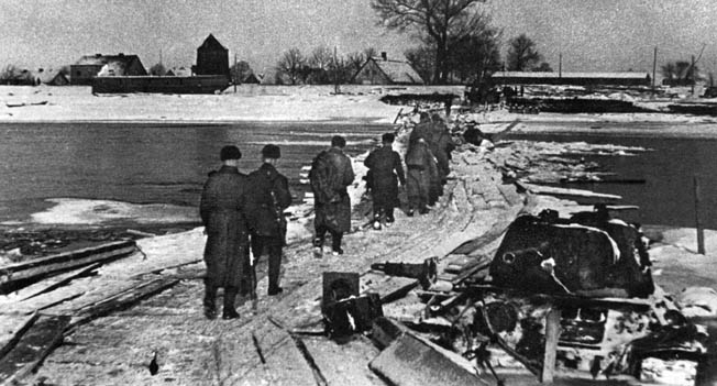 During their pursuit of the retreating Germans, Soviet soldiers cross the Oder River on a pontoon foot bridge. By January 26, 1945, the Red Army had established a line east of the Oder, and within weeks, the final push to Berlin would begin.