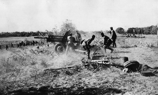 Russian infantry service field artillery and fire small arms at attacking Germans in defense of the Kursk salient.