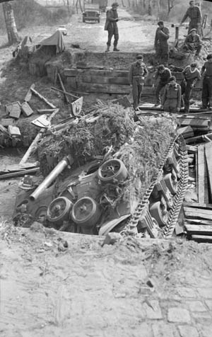During the 21st Army Group drive toward the German city of Bremen, this Sherman tank attempted to cross a stream on an unstable bridge and collapsed it in the process. Armored vehicles that followed were compelled to seek another crossing point.