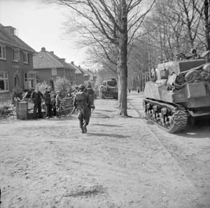 Moving through the Dutch town of Ede on April 17, 1945, Sherman tanks of the 5th Canadian Armored Division and infantrymen of the 11th Royal Scots Fusiliers are watched by civilians newly liberated from five years of brutal and oppressive Nazi occupation.