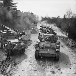 British half-tracks have yielded a dirt road to advancing Stuart light tanks and other vehicles of the 15th Scottish Division. This photo was taken on April 13, 1945, as the Allies advanced toward the Elbe River, deep inside Germany.