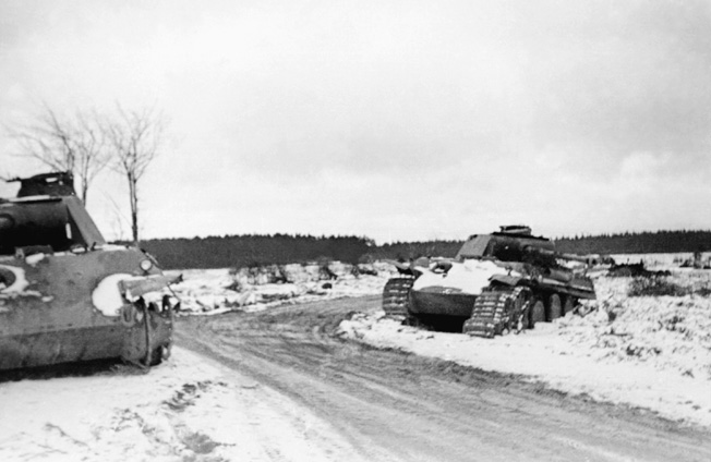 the abttered hulks of Panther tanks 127 (left) and 135 lie abandoned at Lausdell crossroads following the heavy fighting of December 17-18, 1944.