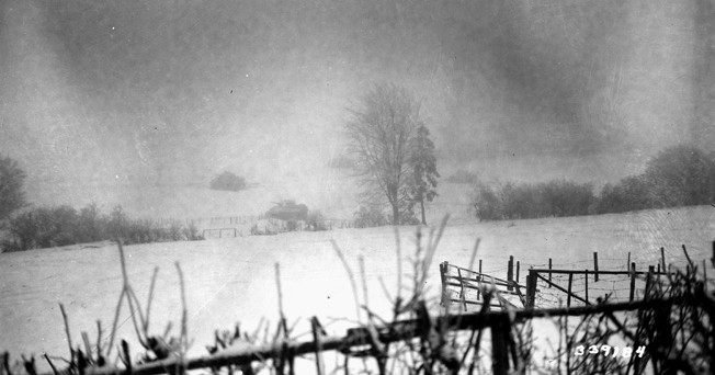 On January 11, 1945, tanks of the U.S. 6th Armored Division move forward in pursuit of the retreating Germans as a snowstorm rages.
