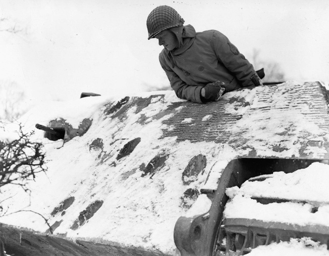 Sergeant George Meyer looks in disbelief at the scars from six direct hits against an enemy Mark VI Tiger tank. The thick armor of the Tiger withstood the successive impacts during the desperate fighting in the Bulge.