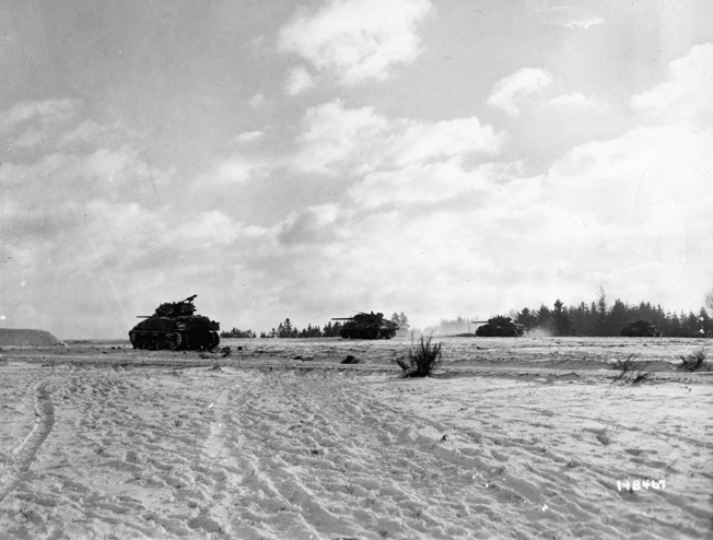 On January 1, 1945, American Sherman tanks fire their 75mm cannon at German positions in the Belgian countryside.