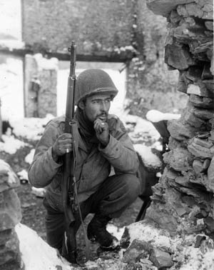Looking for the nest of a German sniper in the Belgian town of Lutrebois, Sergeant Herbert S. Liman of the 134th Regiment, 25th Infantry Division watches for telltale movement.