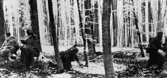 On January 14, 1945, German infantrymen pick their way through a wooded area during the costly Ardennes offensive.