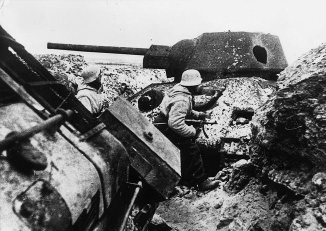 German soldiers pass one of scores of destroyed Red Army tanks near Leningrad. Although Russian losses in armor were severe, Soviet production capacity made good on their replacements.