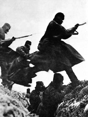 In this photo, typical of those produced for Soviet propaganda purposes, Red Army soldiers uniformed against the cold leap across a trench while their comrades take aim at the invading Germans.