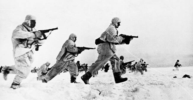 Soviet shock troops, wearing winter camouflage uniforms, sprint across the barren winter landscape in action against German forces.