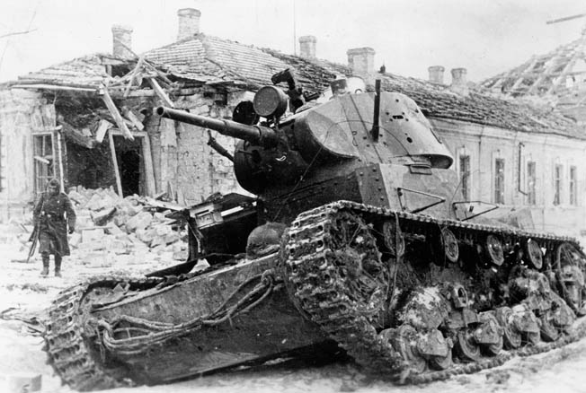 A German soldier seems to ignore the hulk of a Red Army tank knocked out during the fighting around the besieged city of Leningrad. The great city in northern Russia held out during an epic siege that lasted 900 days.