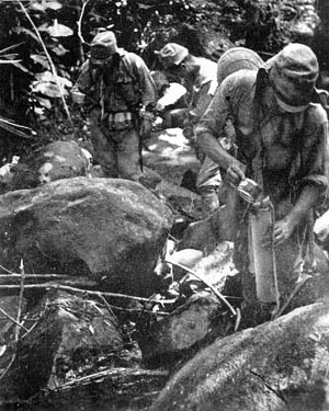 Japanese soldiers, who had previously earned a reputation as expert jungle fighters, fill bamboo canisters with water prior to setting out on a long march through the inhospitable jungle of New Guinea. Disease took a heavy toll in lives and eroded the combat efficiency of soldiers on both sides during the campaign.