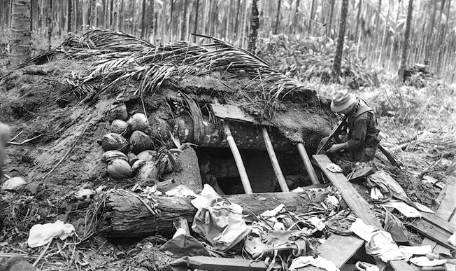 Peering into a pillbox formerly occupied by the Japanese enemy on December 21, 1942, men of the 32nd Infantry Division solidify hard-won territorial gains on New Guinea. The Japanese proved to be a tenacious enemy, and months of bitter fighting lay ahead.