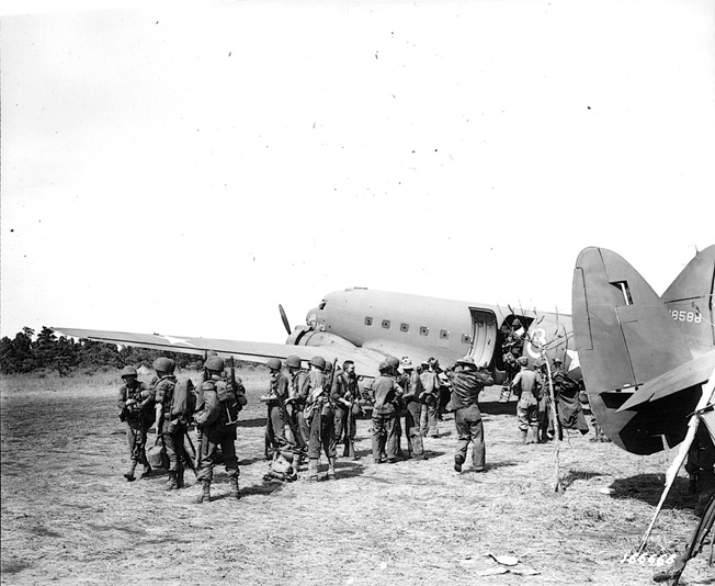 Troops of the 127th Infantry Regiment, 32nd Division, board Douglas C-47 transport aircraft at Dubadura air strip, eight miles from Buna. The soldiers were involved in a large-scale relocation of troops by air during the campaign to secure New Guinea from the Japanese.