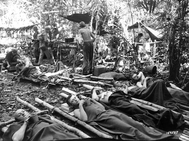 Wounded soldiers of the U.S. 32nd Infantry Division await evacuation at Buna on December 31, 1942.