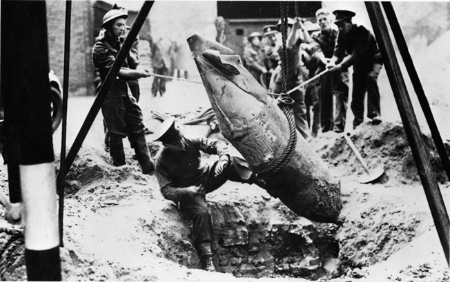 Looking for the fuse of an unexploded 1,200-pound bomb dropped during a German raid on November 25, 1941, Lieutenant R. Davies of London's Bomb Disposal Unit displays nerves of steel. Davies was also credited with saving St. Paul's Cathedral from serious damage by defusing another German bomb.