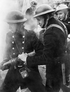 As thick smoke from a raging fire wreaths them, men of the Auxiliary Fire Service attempt to extinguish the blaze after a heavy raid on London during the Blitz.