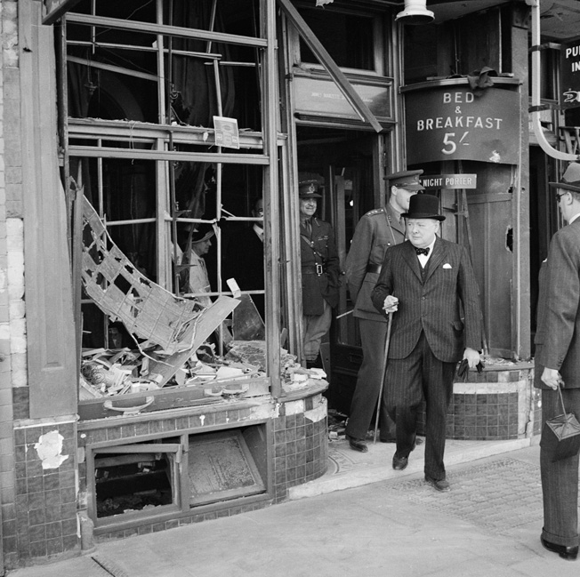 Prime Minister Winston Churchill walks out the front door a bomb-damaged shop in Ramsgate, Kent, following a raid by German bombers on the night of August 28, 1940. Churchill exhorted his people to stand firm against the Nazi aerial onslaught.