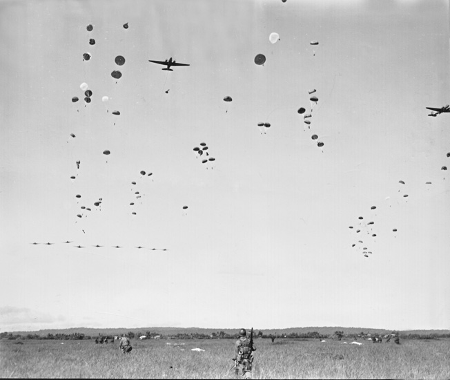 The first wave of airborne troops assembles on the ground as the second wave floats earthward during an operation executed by the 11th Airborne Division in the Philippines. The Los Banos Raid was one of the most flawlessly executed operations involving airborne troops in the history of modern warfare.