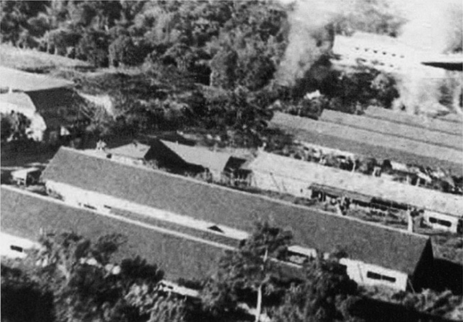 In this photo taken during the Los Banos Raid, buildings inside the prison camp go up in flames. Baker Hall, one of the principal structures at Los Banos is shown in the upper right corner of this image.