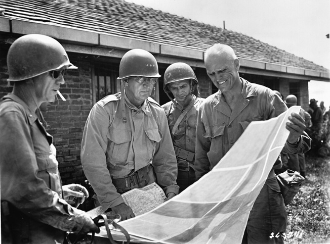 General Robert L. Eichelberger (center), commander of the U.S. Eighth Army in the Philippines and General Joseph Swing, commander of the U.S. 11th Airborne Division, confer during planning for an upcoming operation against the Japanese.
