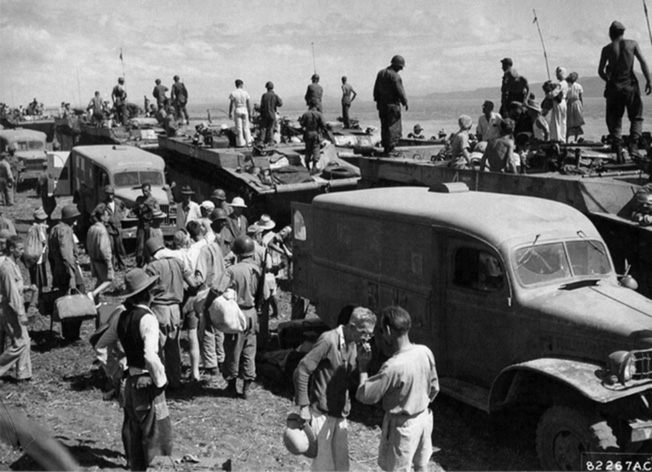 Former Los Banos prisoners exit landing craft at Mamatid where ambulances and medical personnel are standing by. Immediately after their passengers were handed to the medical personnel, the amtracs returned to Los Banos to retrieve the remaining soldiers and former prisoners for another run to freedom.
