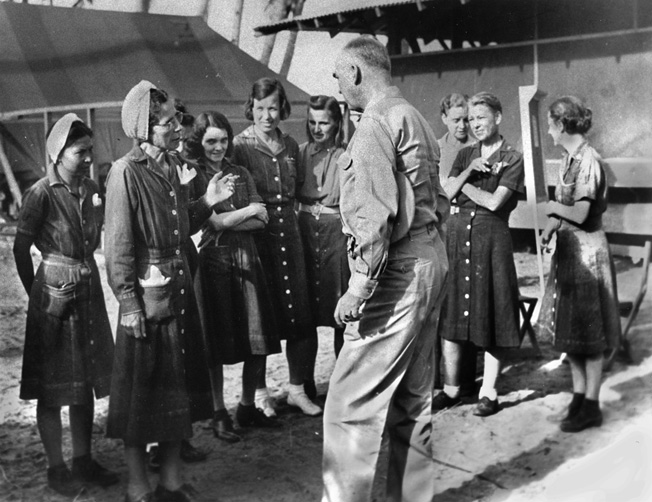 A group of U.S. Navy nurses, the only military personnel detained at Los Banos, talk with Admiral Thomas Kinkaid shortly after their liberation.