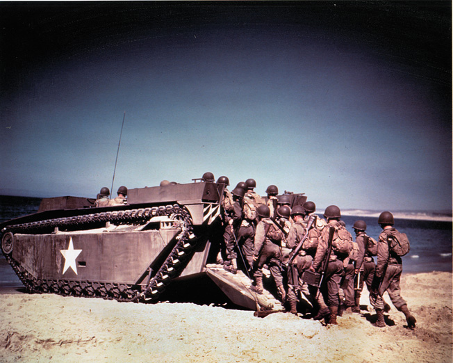 American troops board a tracked landing vehicle during exercises. Ground troops traveling in vehicles such as these executed their portion of the Los Banos Raid in coordination with airborne troops.