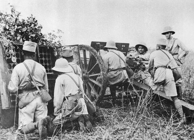 Vichy French forces on Madagascar included both French soldiers and colonial troops from Senegal and other locations. In this photo, colonial soldiers fire a canon under the watchful eye of a French officer in 1942.