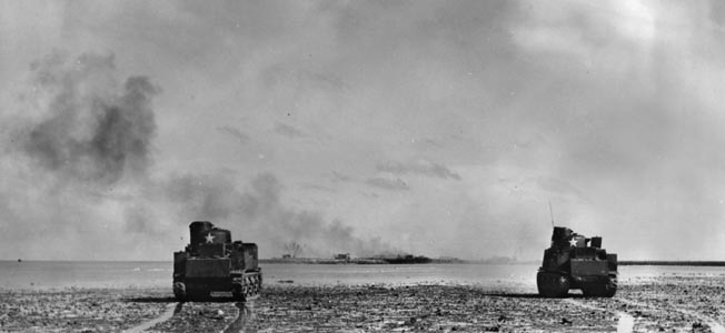 Two Lee medium tanks shell King's Wharf on Butaritari during the second day of combat. Japanese troops had set up machine gun positions near the wharf during the night, to fire on landing barges unloading supplies.