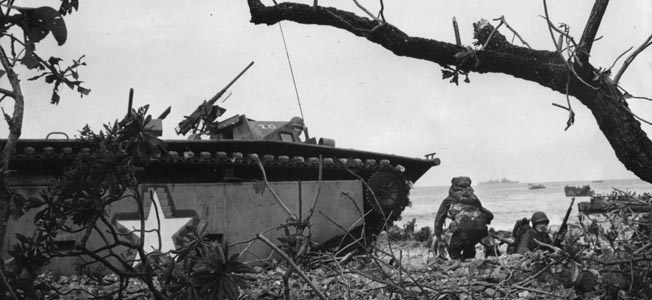 U.S. soldiers move forward on Makin as their amphibious LVT-1 tracked landing craft, nicknamed the Alligator, sits in the foreground. Troops of the 193rd Tank Battalion were detailed to operate the Alligators during the Makin landings.