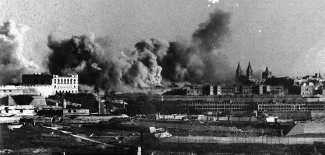 Explosions raise billowing clouds of smoke and flame as Malta endures one of many air raids conducted by German and Italian bombers.