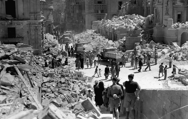 Civilians and military personnel walk through the devastated streets of a Maltese town. At times, the capabilities of British forces to defend the island were nearly decimated.