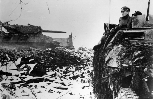 On December 20, 1944, the date of an earlier German attack on Marvie, an advancing German SS armored column rolls past the blackened hulk of an American tank destroyer. German tanks harassed the glider troops defending the town at Marvie but eventually withdrew.