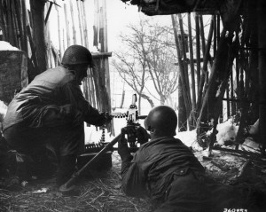 From a position inside a barn near the town of Bastogne, two American soldiers are ready to confront the Germans with their .50-caliber machine gun.
