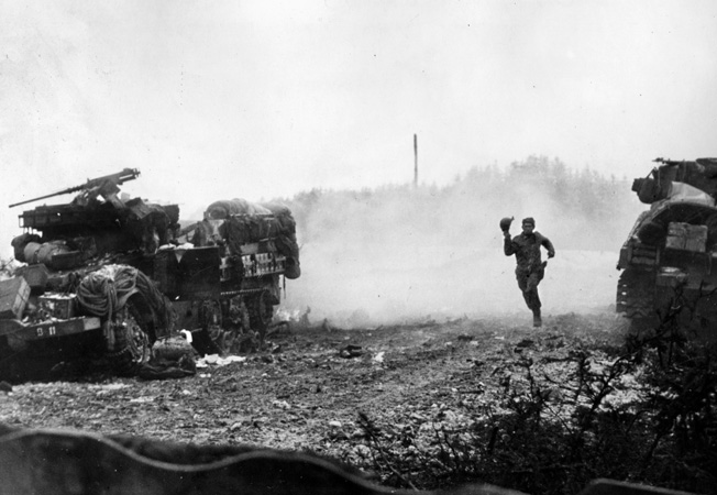 An American soldier on the dead run passes a vehicle that has just taken a direct hit from German artillery.