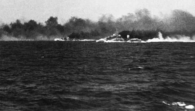 Prior to coming under attack itself, the British cruiser HMS Gloucester was unable to take advantage of a protective smoekscreen seen belching in black and white clouds from the cruisers HMS Ajax and HMAS Perth. In this photograph taken from the deck of the Gloucester, the other British warships are being fired upon by the Italian battleship Vittorio Veneto.