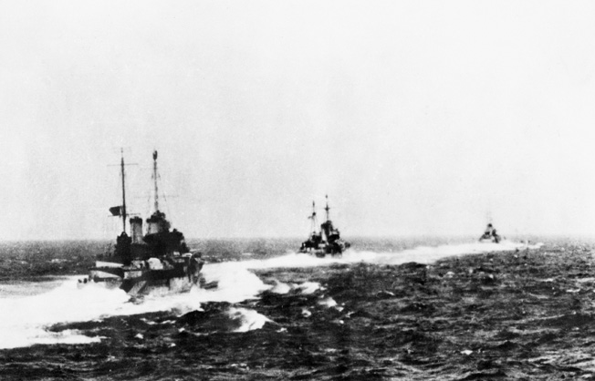 Seen from the deck of the Royal Navy cruiser HMS Gloucester, the British cruisers Ajax and Orion sail in company with the Australian cruiser HMAS Perth.