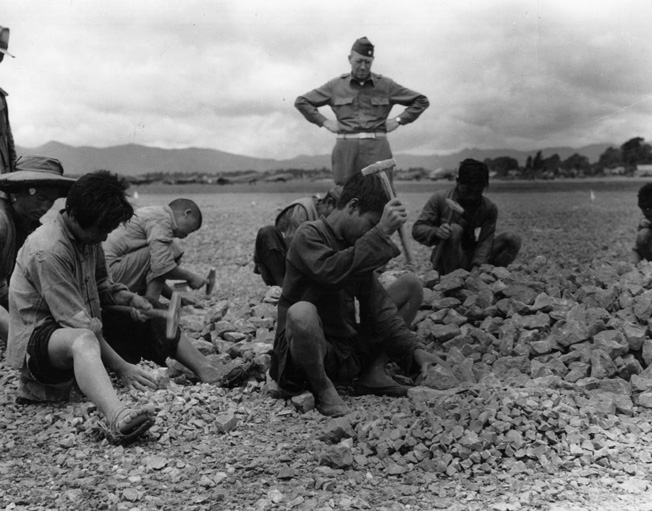 Major Lyman B. Lockwood supervises the tedious wwork of crushing stone for the construction of an airfield in a remote region of China.